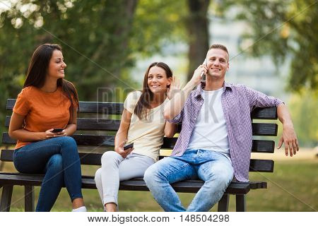 Three friends are sitting on bench in park and using smartphones.