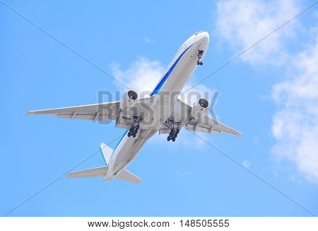 Airplane taking off bottom view and blue sky