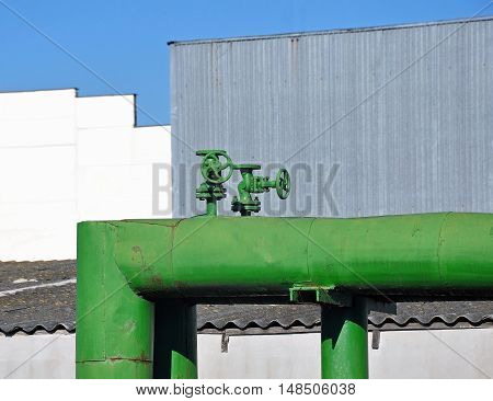 Green painted metal pipe with two valves on the background of the industrial enterprise.