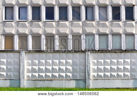 Front view of facade of an industrial building of gray panels. White cellular concrete fence in the foreground.