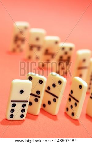White dominoes standing in a row on red background