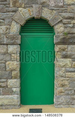 Green door in an old, brick wall