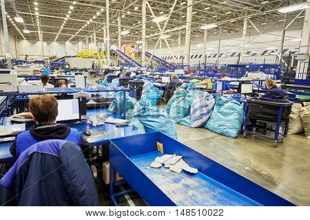 RUSSIA, MOSCOW - DEC 16, 2014: Women work at conveyor with parcels in the automated sorting center in Vnukovo. Moscow Automated sorting center - the largest in Eastern Europe.