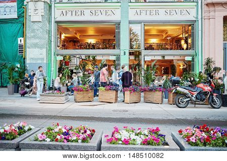 RUSSIA, MOSCOW - JUN 22, 2015: People against facade of After Seven restaurant at Bolshaya Dmitrovka street. Restaurant After Seven - European restaurant with terrace.