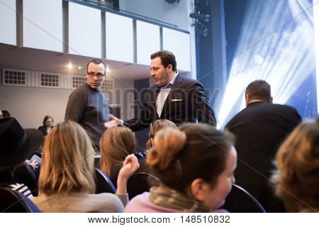 RUSSIA, MOSCOW - APR 14, 2015: Two men are talking near stage and other visitors at Scenary Awards Chernykh (Slovo).