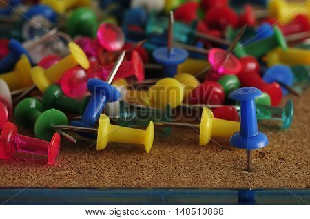 Colorful push pins on a cork board