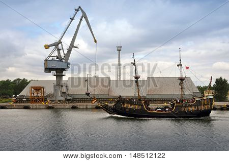 GDANSK, POLAND - JULY 15, 2013: Old stylized ship with tourists on the background of industrial cranes and warehouses against the stormy sky. Gdansk, Poland.