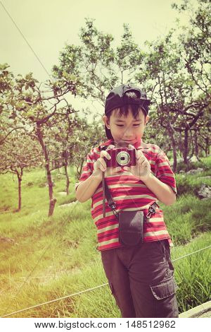Happy asian boy with camera at national park . Child smiling and taking photos by camera outdoors with bright sunlight at the daytime travel on vacation. Vintage effect and cream tone.