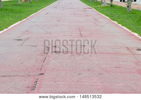 Running track old rubber coating shabby and cracked surface select focus front with shallow depth of field.