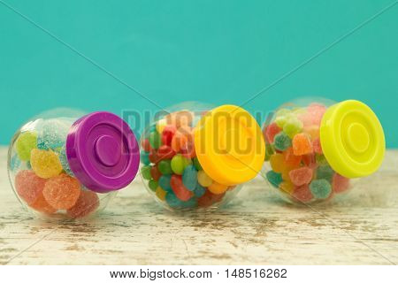 Three glass containers full of jellybeans on wooden table with blue background