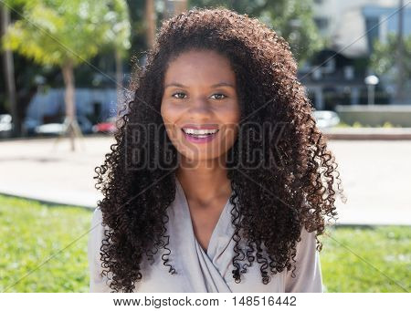 Laughing latin woman with long curly hair outdoor in the city in the summer