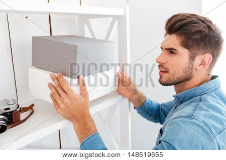 Hanadsome young man putting boxes on the shelf in office