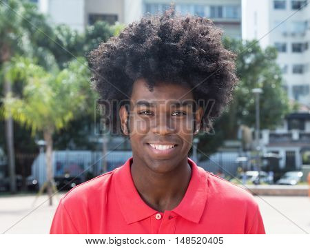 Laughing african young adult with typical afro hairstyle outdoor in the city in the summer