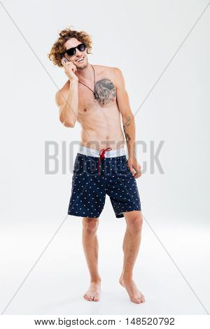 Full length portrait of a smiling curly beach man talking on the phone over white background