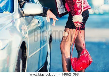 Prostitution - street prostitute talking to customer. horizontal image, toned image,