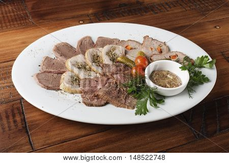 Baked roast beef, chicken rolls, tongue and pork meat with vegetables in a white oval plate. Wooden background.