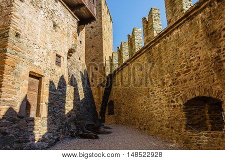 the shadows of the battlements drawn on the towers illuminated by the sun /FENIS,ITALIA-SEPTEMBER 5 .The facade of the castle of Fenis in Aosta Valley with its city walls and its defensive towers  on September 5 2016 in Fenis.