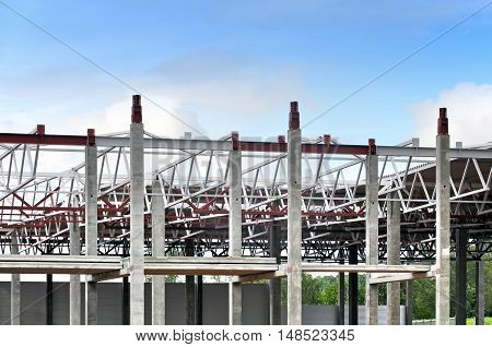 The process of of erection of a frame-span multistory building. Monolithic concrete columns and metal girders against the blue sky.
