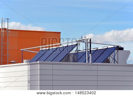 Modern industrial building with panels of tubes for water heating on the roof.