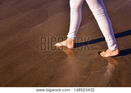 Lonely woman walking along on the beach