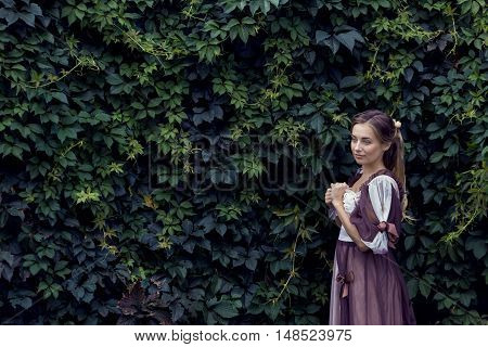 Young woman outdoors background is green fence arborvitae. Beautiful woman on a background of green hedge