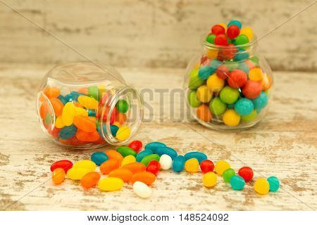 Many candy in glass with differents colors on wooden background
