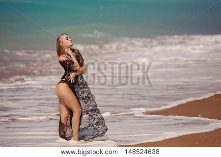 Elegant lady with perfect body laying at the beach. Evening photo during sunset