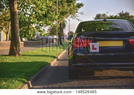 A car with the L plates on ready for a new driver to use.