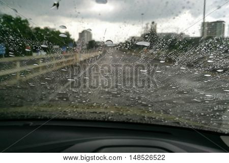 Road view through car window blurry with heavy rain, Driving in rain, rainy weather