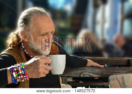Good looking senior having a cup of coffe in a restaurant terrace looking a little bit anxious