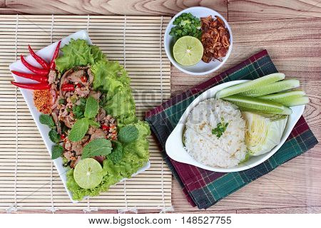Sticky rice with spicy sour mixed herb salad of chicken and liver chicken . Top view.