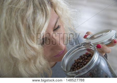 Blonde girl with curly hair is smelling coffee beans in glass pot