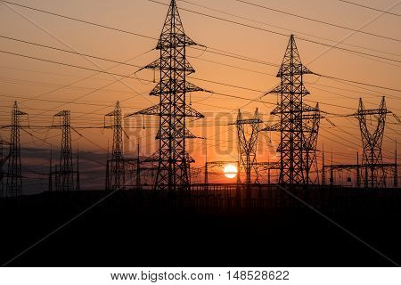 Electricity transmission pylon silhouetted against sunset sky. Sunset background.