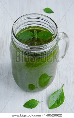 Healthy eating green smoothie with basil in a glass jar