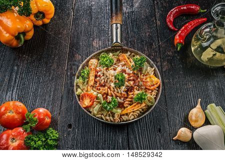 Fusilli pasta cooked with fresh vegetable in frying pan and ingredients on the dark wooden table