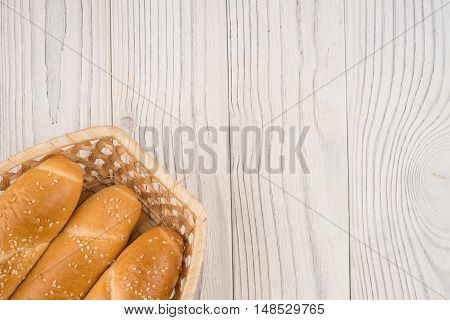 Buns in a wicker basket on old wooden table. Top view.