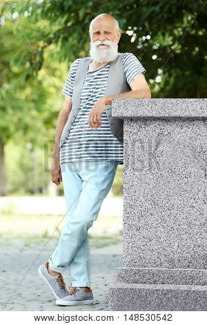 Elderly bearded man in stylish clothes on sunny day at park