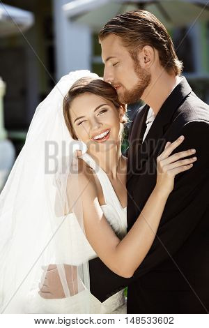 Happy beautiful newlyweds smiling, embracing, kissing outside. Copy space