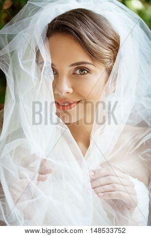 Young beautiful blonde bride in wedding dress and veil smiling, looking at camera. Copy space.