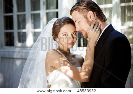 Young beautiful newlyweds in suit and wedding dress smiling, enjoying, embracing. Copy space.