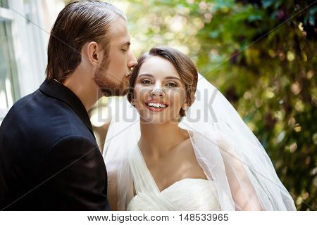 Beautiful newlyweds in suit and wedding dress smiling, kissing in park. Copy space.