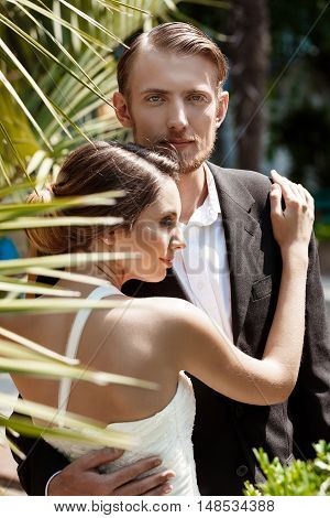 Young beautiful couple of newlyweds smiling, embracing in park. Copy space.