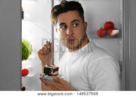 Handsome man eating cake in kitchen. Unhealthy food concept