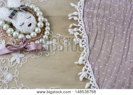Brooch like head of hare with bracelets on pink lace as background