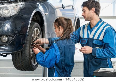 Young male and female mechanics changing tire from suspended car at garage