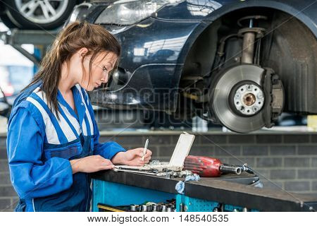 Young female mechanic making notes with car in background at garage