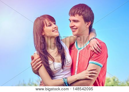 Young happy couple enjoying hugging outdoors over blue sky