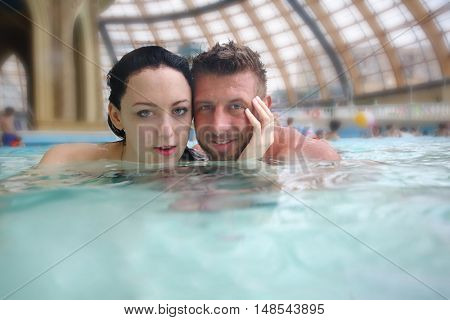 Man and woman swimming in the pool at the aquapark