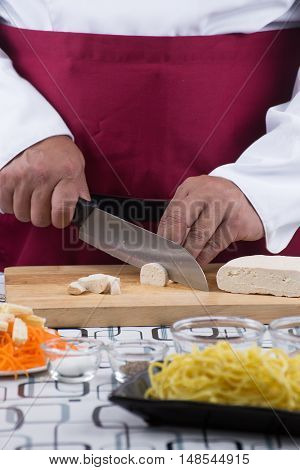 Chef slicing tofu for cooking / cooking stir fry vegetarian noodle concept