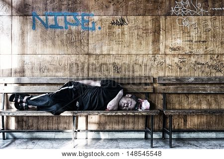 Homeless Man Sleeping on the Wooden Bench in the Train Station